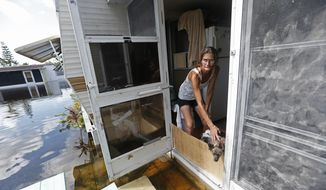 In this Sept. 12, 2017, photo, Cherie Ethier stands in a doorway of her mobile home with her dogs and cats, surrounded by floodwater, in the Marco Naples RV Resort, in the aftermath of Hurricane Irma, in Naples, Fla. Ethier and her husband stayed in a hotel during the storm, but returned to their trailer as soon as they could. (AP Photo/Gerald Herbert)