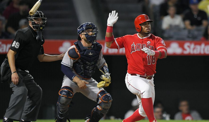 Los Angeles Angels' Luis Valbuena, right, tosses his bat after hitting a double as Houston Astros catcher Max Stassi, center, watches along with home plate umpire Cory Blaser during the fourth inning of a baseball game, Wednesday, Sept. 13, 2017, in Anaheim, Calif. (AP Photo/Mark J. Terrill)