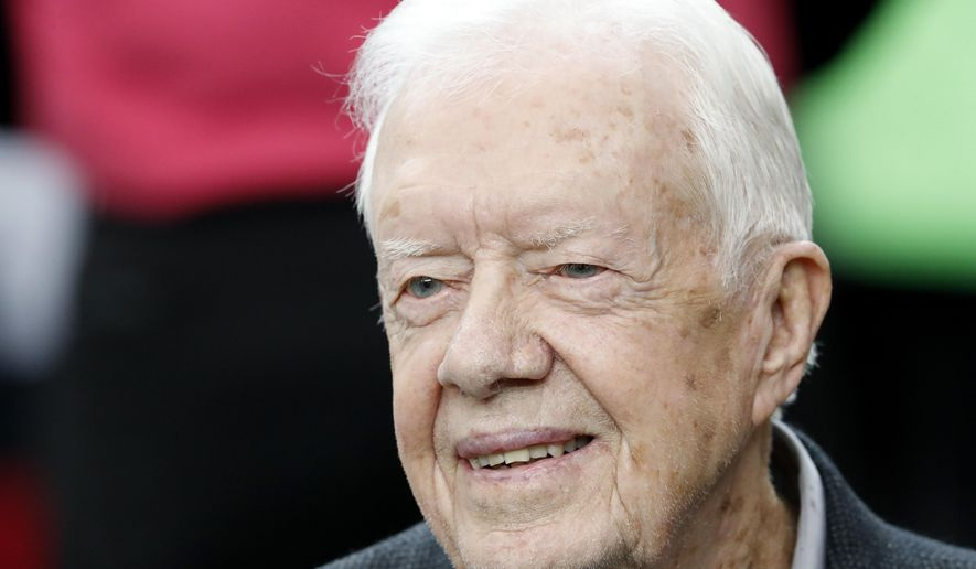 In this Oct. 23, 2016, file photo, former President Jimmy Carter sits on the Atlanta Falcons bench before the first half of an NFL football game between the Atlanta Falcons and the San Diego Chargers, in Atlanta. (AP Photo/John Bazemore, File)