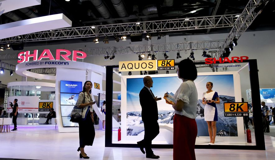 In this Thursday, Sept. 7, 2017, photo, visitors walk by Foxconn's exhibition booth promoting its Sharp 8K flat screen TV in Beijing. The Wisconsin Senate approved nearly $3 billion in cash payments for Foxconn Technology Group on Tuesday, Sept. 12, 2017 while also giving the Taiwanese company a slightly less expedited path to the state Supreme Court for certain legal challenges related to a planned massive electronics manufacturing factory. (AP Photo/Andy Wong)