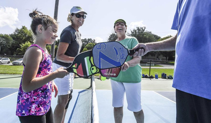 In this Aug. 12, 2017 photo, Natalie Alexander, left, celebrates with others after a game of  pickle ball at Cresthaven Park in Decatur, Ill.Since Decatur Pickleball was founded in 2014, popularity of the sport has blossomed locally. While more than 100 people are associated with the group today. Created in the 1950s, the sport is a hybrid of tennis, badminton and pingpong that has become so popular in the United States, that it even has its own governing body, the United States of America Pickleball Association. (Clay Jackson/Herald & Review via AP)