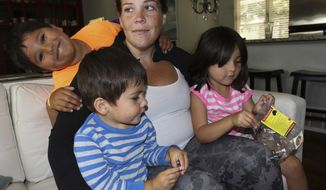 In this Sept. 4, 2017 photo, Colleen Tyrrell Llacas spends time with her three children,  Samuel, left, Joshua, center, and Lucy Jane, right, at their home in Naperville, Ill. For more than two years Colleen has been suffering from a cerebral spinal fluid leak, which has caused her a debilitating list of symptoms that initially were misdiagnosed as migraines. (Bev Horne/Daily Herald, via AP)