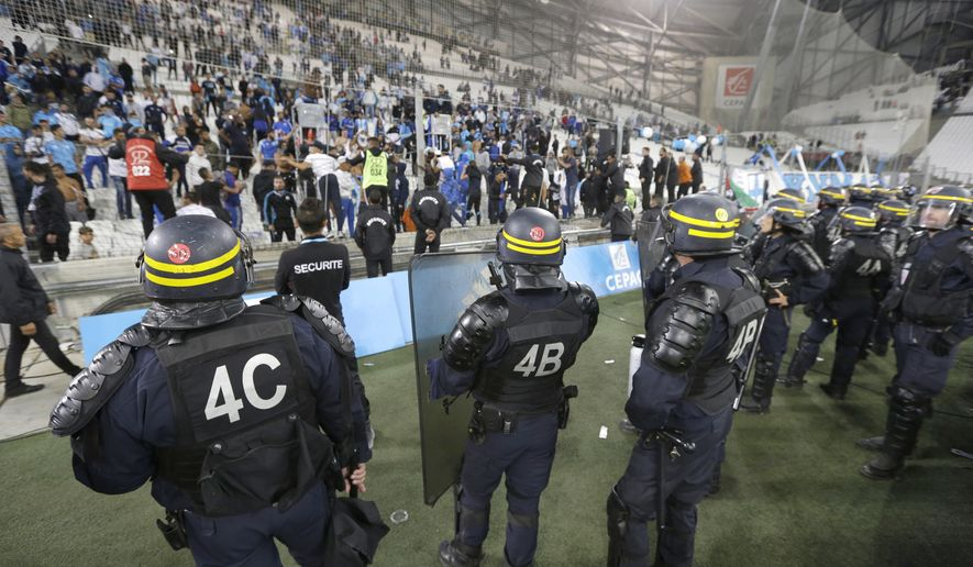 Riot police secure after the League One soccer match between Marseille and Rennes, at the Velodrome stadium, in Marseille, southern France, Sunday, Sept. 10, 2017. (AP Photo/Claude Paris)