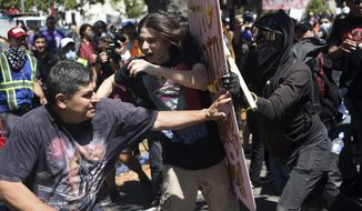 FILE - In this Sunday, Aug. 27, 2017, file photo, demonstrators clash during a free speech rally, in Berkeley, Calif. Police in the city of Berkeley can use pepper spray on violent demonstrators after the City Council voted Tuesday, Sept. 12, to allow police to use pepper spray to repel attacks on officers and others during the kind of violent protests that have rocked the city this year. (AP Photo/Josh Edelson)