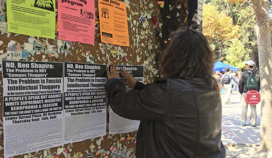 "In this Sept. 8, 2017, photo, a woman tapes flyers on a University of California, Berkeley campus bulletin board calling for a protest against right-wing speaker Ben Shapiro in Berkeley, Calif. The university will seal off large parts of its campus like a fortress with a closed perimeter and a ""very large"" visible police presence Thursday, Sept. 14. City and campus authorities anticipate demonstrations at a speech by conservative commentator Ben Shapiro, a former Breitbart editor, and are preparing for possible violence with a variety of new strategies and tightened security. (AP Photo/Jocelyn Gecker)"