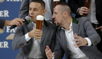 Bayern's Rafinha, left, and Franck Ribery sing a birthday song for team mate Thomas Mueller in traditional Bavarian clothes during a photo shooting of a beer brewing company in Munich, Germany, Wednesday, Sept. 13, 2017. Mueller celebrates his 28th birthday today. (AP Photo/Matthias Schrader)