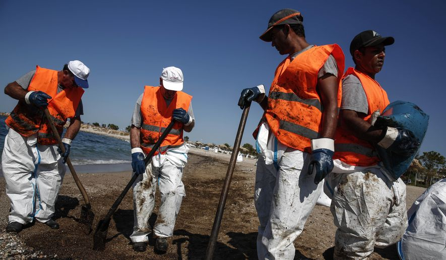 Workers clean a beach from an oil spillage at Faliro suburb, near Athens, on Thursday,Sept. 14, 2017. Greek authorities insist they are doing everything they can to clean up pollution caused by an oil spill following the sinking of a small oil tanker that has left large sections of the Greek capital's coastal areas coated in viscous, foul-smelling oil. (AP Photo/Yorgos Karahalis)