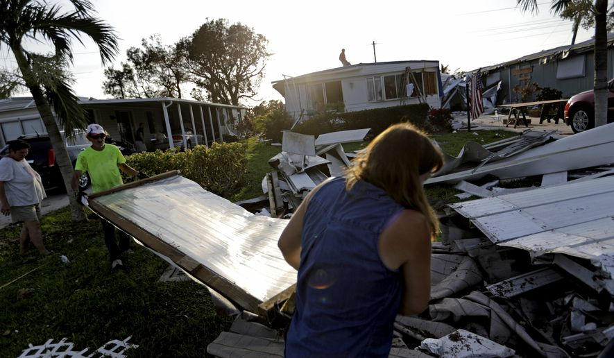 Joseph Ross, left, cleans up debris from his damaged home with help from a neighbor in the aftermath of Hurricane Irma in Naples, Fla., Wednesday, Sept. 13, 2017. (AP Photo/David Goldman)