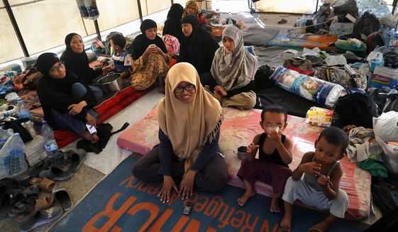 FILE - In this file picture taken on Monday, July 24, 2017, an Indonesian family who escaped from the Islamic State group in Raqqa gather inside their tent at a refugee camp, in Ain Issa, Syria. The family spent nearly two years with the Islamic State group in Syria and has denounced IS militants as interested only in power, money and sex in a video released by Indonesia's counterterrorism agency. The family was detained at the agency's de-radicalization center near the capital, Jakarta, after returning to Indonesia in mid-August and was released on Wednesday. (AP Photo/Hussein Malla, File)