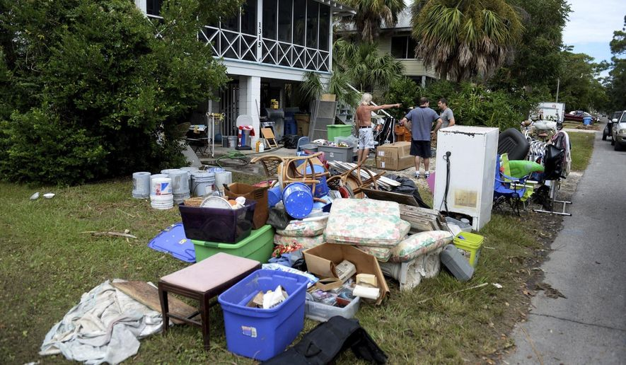 David Fettke, left, and his wife, Sonya, spend Wednesday, Sept. 13, 2017, airing out the lower level of their home on Tybee Island and putting flood-damaged items on their lawn. Storm surge flooded hundreds of homes near beaches and marshes, sunk numerous boats and trashed docks on the Georgia coast even though Irma was a weakened tropical storm when its center crossed the state more than 100 miles (160 kilometers) inland. (Dash Coleman/Savannah Morning News via AP)