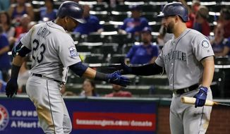 Seattle Mariners' Nelson Cruz (23) is congratulated by Yonder Alonso after Cruz hit a solo home run off Texas Rangers relief pitcher A.J. Griffin during the seventh inning of a baseball game, Thursday, Sept. 14, 2017, in Arlington, Texas. (AP Photo/Tony Gutierrez)