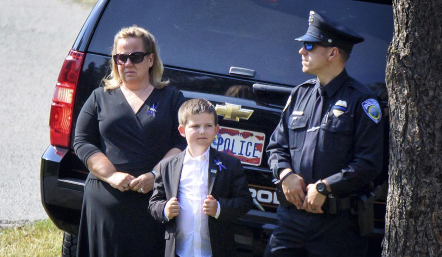 Shawn Mathews, and her son Wyatt, center, wait for her husband's casket to arrive for burial ceremony at Summit Park Cemetery, Thursday, Sept. 14, 2017, in Wayzata, Minn. Wayzata police officer William Matthews, 47 was struck and killed last week while removing debris from a highway. (Glen Stubbe/Star Tribune via AP)