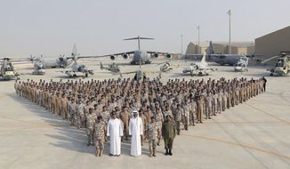 In this Monday, Sept. 11, 2017 photo released by Qatar News Agency, QNA, the Qatari Emir Sheikh Tamim bin Hamad Al Thani, centre front, poses for a photo with Emiri Air Force at al-Udeid Air Base in Doha, Qatar. Sheikh Tamim bin Hamad Al Thani's visit to al-Udeid Air Base throws into sharp relief the delicate balancing act the U.S. faces in addressing the Qatar crisis. (QNA via AP)
