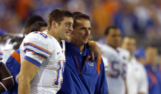 In this Nov. 1, 2008, file photo, Florida quarterback Tim Tebow, left, and coach Urban Meyer celebrate in the fourth quarter against Georgia during an NCAA college football game in Jacksonville, Fla. Florida beat Georgia 49-10, the season after Georgia defeated Florida 42-30. (AP Photo/Stephen Morton, File) **FILE**