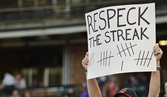 Cleveland Indians fan Matthew Van Worner holds a sign before a baseball game between the Cleveland Indians and Kansas City Royals, Thursday, Sept. 14, 2017, in Cleveland. (AP Photo/David Dermer)