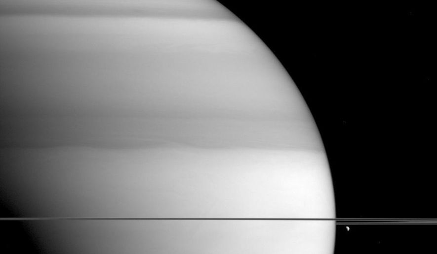 This Sept. 6, 2015 image made available by NASA shows bright-and-dark bands in the atmosphere of Saturn, as seen from the Cassini spacecraft. This image was taken in wavelengths of light that are absorbed by methane. Dark areas are regions where light travels deeper into the atmosphere, passing through more methane. The moon Dione is at right. At bottom are shadows of the planet's rings. (NASA/JPL-Caltech/Space Science Institute via AP)