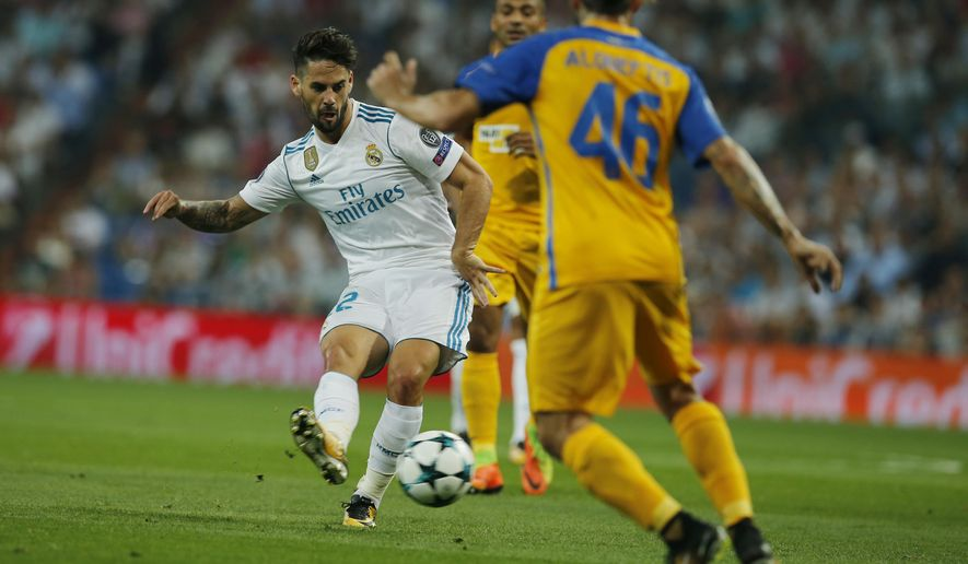 Real Madrid's Isco, left, passes the ball during a Champions League group H soccer match between Real Madrid and Apoel Nicosia at the Santiago Bernabeu stadium in Madrid, Spain, Wednesday, Sept. 13, 2017. (AP Photo/Paul White)
