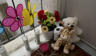 Candles and stuff animals of a makeshift memorial sit outside an apartment Thursday, Sept. 14, 2017, where three children were killed, in West Sacramento, Calif. The children are killed around 9 p.m. Wednesday, and their father Robert Hodges, 33, has been arrested in the deaths that followed a domestic violence altercation with his wife. (AP Photo/Rich Pedroncelli)