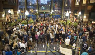 In this Wednesday, Sept. 13, 2017 photo, hundreds gather in the atrium of River Park Square for a candlelight vigil in support of the victims of the Freeman High School, in Rockford, Wash., shooting that occurred earlier in the morning and claimed the life of one student and injured three others. (Colin Mulvany /The Spokesman-Review via AP)