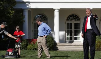 Frank Giaccio, 11, of Falls Church, Va., left, is assisted by a member of the National Park Service, and his father Greg Giaccio, as he gets back to mowing the lawn after President Donald Trump said goodbye, Friday, Sept. 15, 2017, in the Rose Garden at the White House in Washington. The 11-year-old, who wrote the president requesting to mow the lawn at the White House, was so focused on the job at hand the he didn't notice the president until he was right next to him. (AP Photo/Jacquelyn Martin)