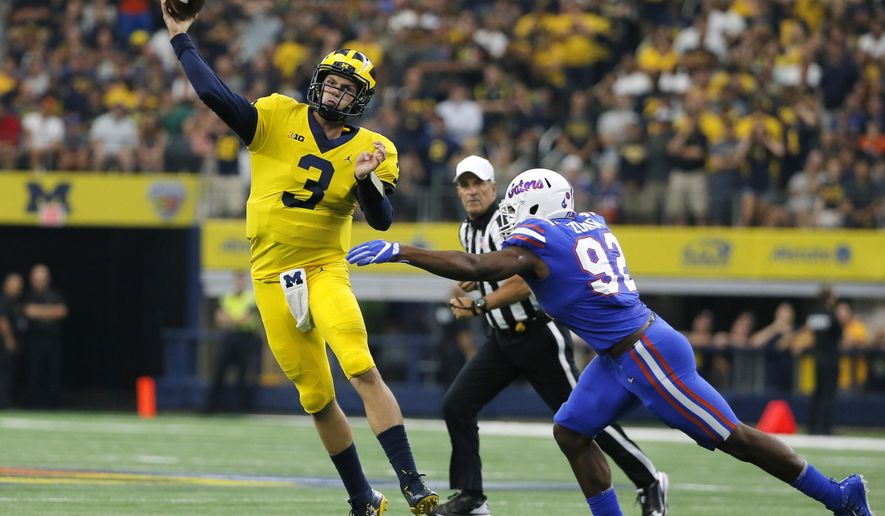 FILE - In this Sept. 2, 2017, file photo, Michigan quarterback Wilton Speight (3) throws a pass under pressure form Florida defensive lineman Jabari Zuniga (92) during an NCAA college football game in Arlington, Texas.  No. 7 Michigan must prove it can pass after Speight struggled in the first two games, barely completing half his passes and throwing only one more touchdown than interception. Speight will get a shot against Air Force, which has won seven straight and is aiming to beat its highest-ranked opponent since knocking off No. 6 Stanford in 1970. (AP Photo/Tony Gutierrez, File)