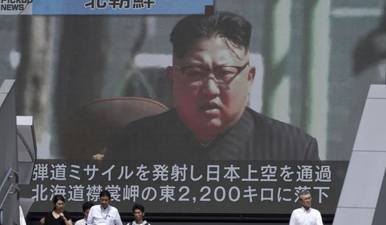People walk past a public TV screen showing a file footage of North Korean leader Kim Jong Un during news on North's missile launch, in Tokyo, Friday, Sept. 15, 2017. North Korea fired an intermediate-range missile over Japan into the northern Pacific Ocean on Friday, U.S. and South Korean militaries said, its longest-ever such flight and a clear message of defiance to its rivals. (AP Photo/Eugene Hoshiko)