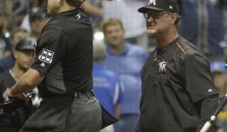 Home plate umpire Seth Buckminster ejects Miami Marlins manager Don Mattingly from the game during the eighth inning of a baseball game Friday, Sept. 15, 2017, in Milwaukee. (AP Photo/Morry Gash)