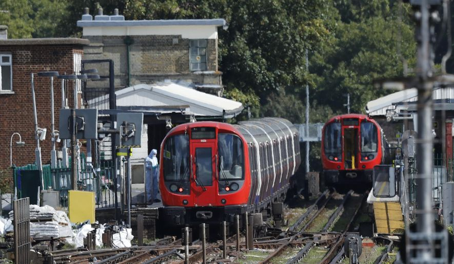 A police forensic officer stands beside the train, at left, where an incident happened, that police say they are investigating as a terrorist attack, at Parsons Green subway station in London, Friday, Sept. 15, 2017. A bucket wrapped in an insulated bag caught fire on a packed London subway train Friday, sending commuters stampeding in panic at the height of the morning rush hour. (AP Photo/Frank Augstein)