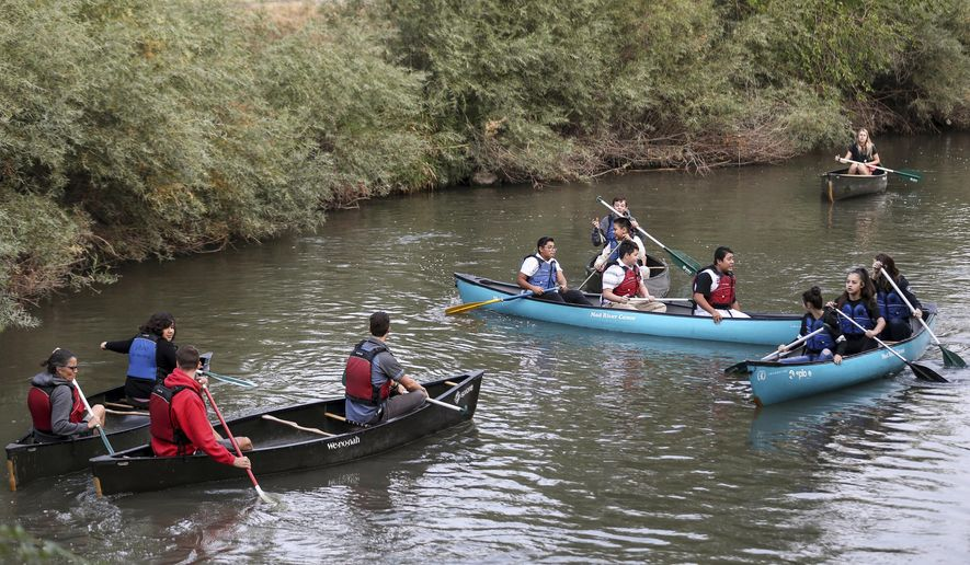 A group of students from Northwest Middle School and guides from Splore and the National Ability Center paddle canoes on the Jordan River in Salt Lake City on Thursday, Sept. 7, 2017.   The canoeing trip was part of the Get Into the River Festival, a monthlong celebration featuring the Jordan River and the Jordan River Parkway. Throughout September, cities and counties along the river host events that help celebrate and raise awareness about the Jordan River.  (Spenser Heaps/The Deseret News via AP)