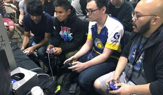 "In this Aug. 25, 2017, photo, Connor Nguyen, at right, and Griffin Williams, second from right, compete in a ""Super Smash Bros. Melee"" tournament at the Shine eSports festival at the Seaport World Trade Center in Boston. Griffin, 21, is captain of an esports team at the University of California, Irvine, and Nguyen, 23, is a graduate of the school. The University of California, Irvine, is among a growing number of U.S. schools starting to offer at least partial scholarships to students who compete in esports, competitive video-game playing. (AP Photo/Collin Binkley)"