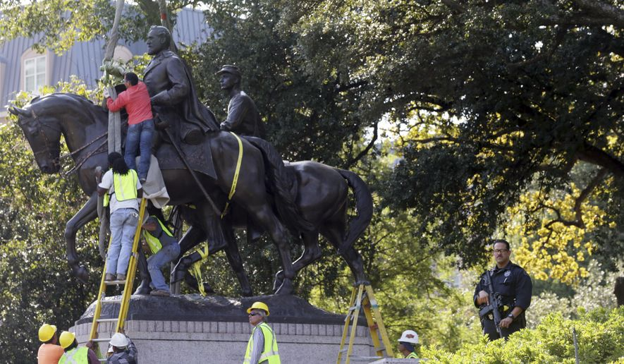 Workers prepare for the removal of a statue of Robert E. Lee at a public park in Dallas, Thursday, Sept. 14, 2017. (AP Photo/LM Otero)