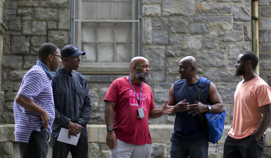 In this Aug. 12, 2017, photo, John Pace, a former juvenile lifer, left, stands with members of the re-entry support group he started in May after being released from prison in February at Myers Recreation Center, in Philadelphia. From left to right are John Pace, Jeffrey Dean, Vincent Boyd, Charles Brown, Stacey Torrance. (Margo Reed/The Philadelphia Inquirer via AP)