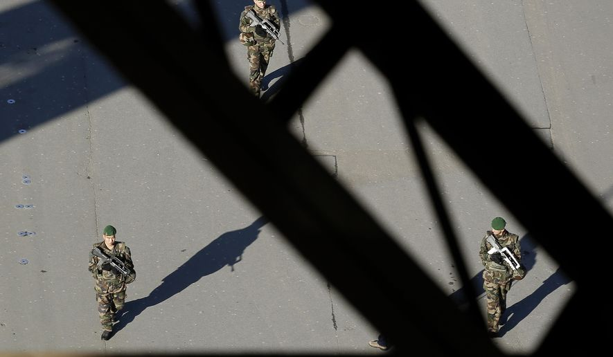 FILE - In this Monday Nov. 23, 2015 file photo, French soldiers patrol under the Eiffel Tower in Paris. Paris police say a knife-wielding assailant tried to attack a soldier in a major subway interchange but was quickly arrested and no one was hurt. (AP Photo/Laurent Cipriani, File)