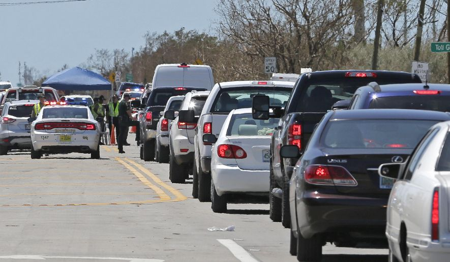 Motorists line up to enter the Florida Keys at a checkpoint in the aftermath of Hurricane Irma, Thursday, Sept. 14, 2017, in Florida City, Fla. Residents of the Florida Keys continue to be turned away. (AP Photo/Alan Diaz)