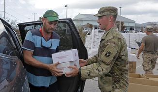 A member of the National Guard hands over boxes of food to Patrick Garvey in the aftermath of Hurricane Irma, Thursday, Sept. 14, 2017, in Big Pine Key, Fla. (AP Photo/Alan Diaz)
