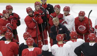 Carolina Hurricanes coach Bill Peters speaks with players during the NHL hockey team's training camp in Raleigh, N.C., Friday, Sept. 15, 2017. (AP Photo/Gerry Broome)