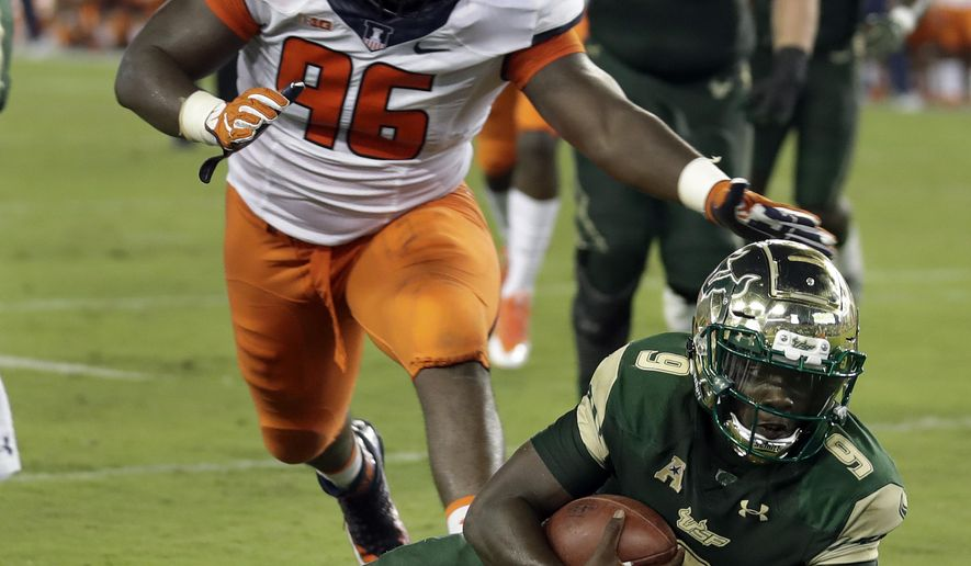 South Florida quarterback Quinton Flowers (9) dives past Illinois defensive lineman Tymir Oliver (96) on a 6-yard touchdown run during the second quarter of an NCAA college football game Friday, Sept. 15, 2017, in Tampa, Fla. (AP Photo/Chris O'Meara)