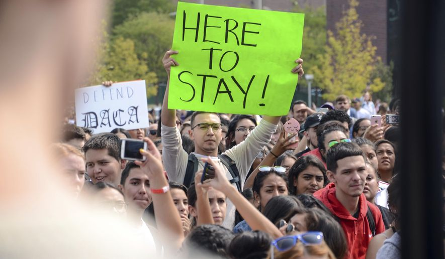 In this Sept. 5, 2017, file photo, a protester holds a sign at a rally at Metropolitan State University after President Donald Trump's decision to repeal a program protecting young immigrants from deportation in Denver. (AP Photo/Tatiana Flowers, File)