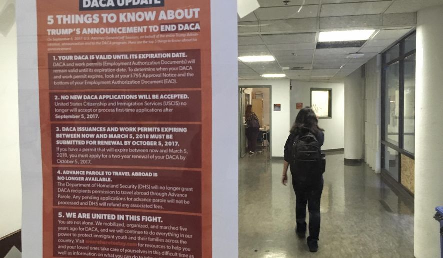 """In this photo taken Sept. 7, 2017, a student walks past a tip sheet for Deferred Action for Childhood Arrivals recipients who fear deportation that is taped to a window on the University of California, Berkeley campus in Berkeley, Calif. Colleges and universities nationwide are stepping up efforts to help the students who are often called """"Dreamers,"""" after the Trump administration announced plans last week to end that federal program protecting immigrants brought to the U.S. illegally as children. (AP Photo/Jocelyn Gecker)"""