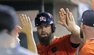 Houston Astros' Evan Gattis is congratulated in the dugout after scoring during the sixth inning of a baseball game against the Seattle Mariners, Friday, Sept. 15, 2017, in Houston. (AP Photo/David J. Phillip)