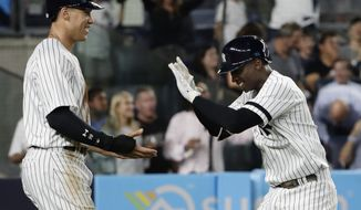 New York Yankees' Aaron Judge, left, celebrates with Didi Gregorius, after they scored on home run by Gregarius during the fifth inning of a baseball game against the Baltimore Orioles, Friday, Sept. 15, 2017, in New York. (AP Photo/Frank Franklin II)