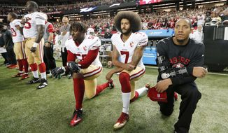 FILE - In this Dec. 18, 2016, file photo, San Francisco 49ers quarterback Colin Kaepernick (7) and outside linebacker Eli Harold (58) kneel during the playing of the national anthem before an NFL football game against the Atlanta Falcons in Atlanta. The blackballed quarterback was honored as Week 1 Community MVP by the players' union for his latest $100,000 donation and a back-to-school giveaway in New York City.  (AP Photo/John Bazemore, File)