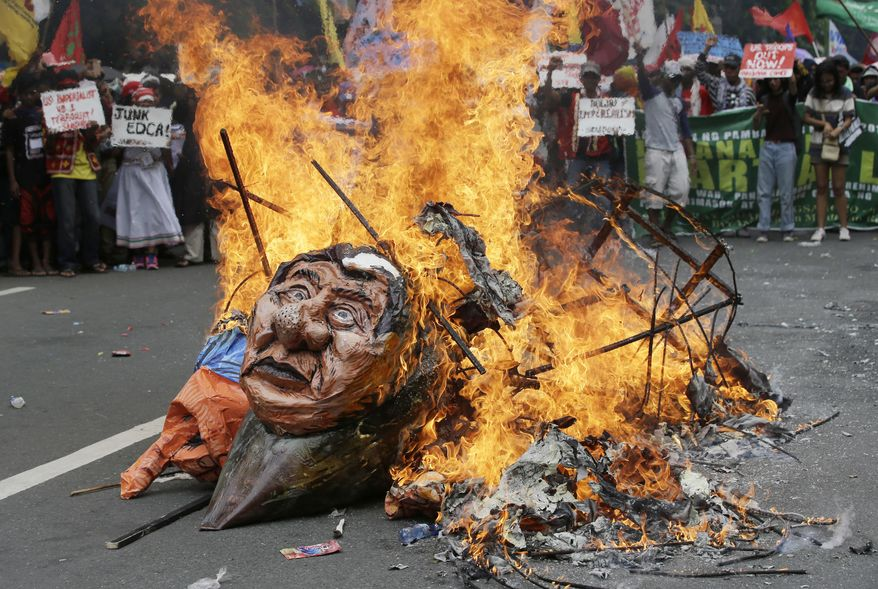 Protesters burn an image of Philippine President Rodrigo Duterte as they tried to march toward U.S. Embassy in Manila, Philippines, Friday, Sept. 15, 2017. The groups is protesting against the alleged increasing intervention of the U.S. military in the ongoing war in Marawi and growing presence in Mindanao. (AP Photo/Aaron Favila)
