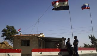 In this Wednesday, Sept. 13, 2017 photo Syrian and Russian flags wave as local residents stand at the check-point of the de-escalation zones near Homs, Syria. Hundreds of people, mostly women and elderly men, living on the both sides which recently was a frontline between Syrian government forces and the Free Syrian Army flocked to a Russian military police check-point on Wednesday to get Russian food aid. (AP Photo/Nataliya Vasilyeva)