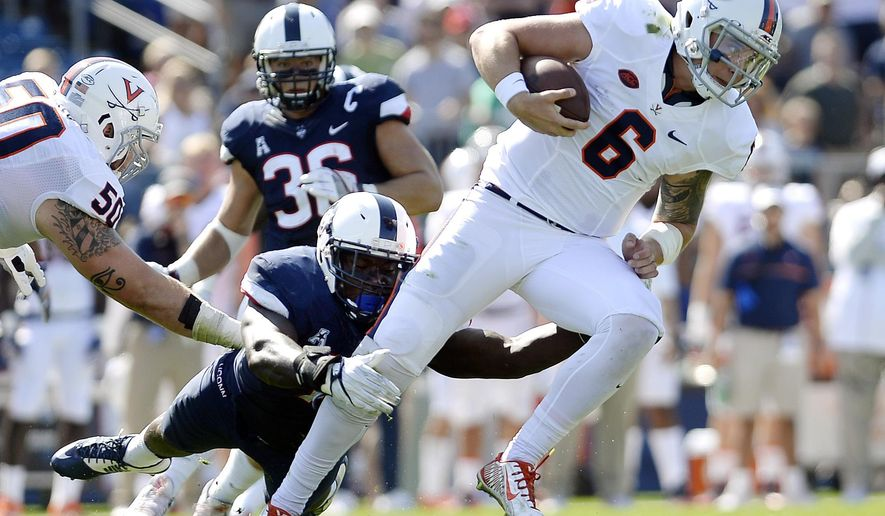 FILE - In this Sept. 17, 2016, file photo, Connecticut's Junior Joseph, left, tackles Virginia quarterback Kurt Benkert (6) during the first half of an NCAA college football game at Pratt & Whitney Stadium at Rentschler Field in East Hartford, Conn. The two teams meet on Saturday. (AP Photo/Jessica Hill, File)