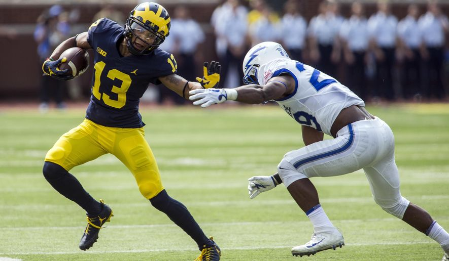 Michigan wide receiver Eddie McDoom (13) tries to hold back a tackle from Air Force defensive back Kyle Floyd (29) in the second quarter of an NCAA college football game in Ann Arbor, Mich., Saturday, Sept. 16, 2017. (AP Photo/Tony Ding)