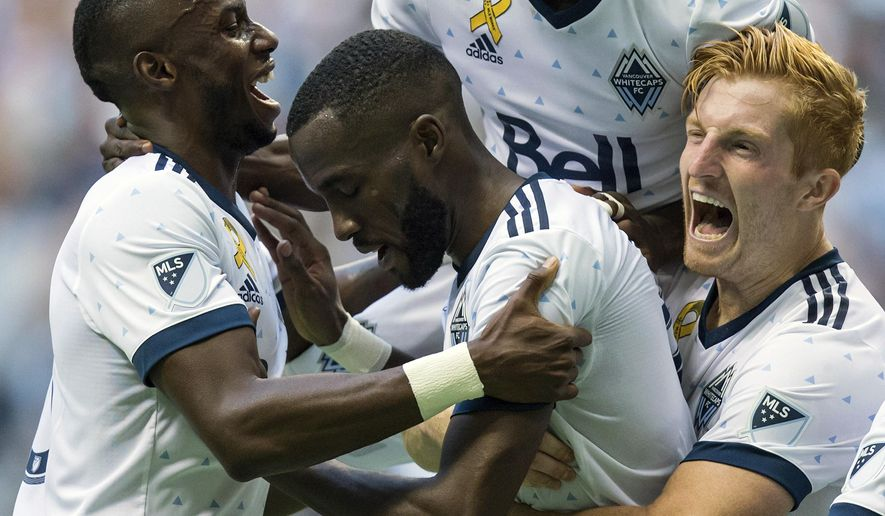 From left to right, Vancouver Whitecaps' Bernie Ibini, Tony Tchani, Alphonso Davies and Tim Parker celebrate Tchani's tying goal against the Columbus Crew during the second half of an MLS soccer game in Vancouver, British Columbia, Saturday, Sept. 16, 2017. (Darryl Dyck/The Canadian Press via AP)