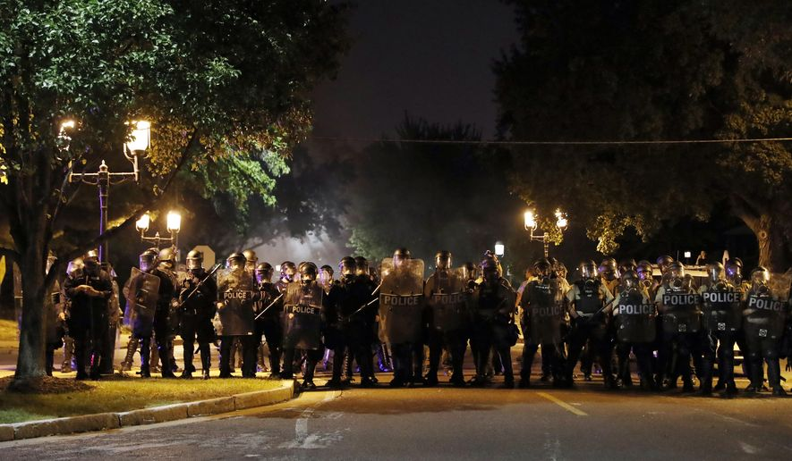 Police line up as protesters gather, Friday, Sept. 15, 2017, in St. Louis, after a judge found a white former St. Louis police officer, Jason Stockley, not guilty of first-degree murder in the death of a black man, Anthony Lamar Smith, who was fatally shot following a high-speed chase in 2011. (AP Photo/Jeff Roberson)