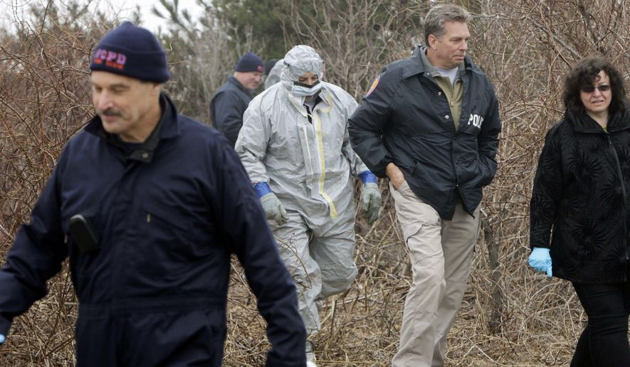 FILE - In this April 11, 2011, file photo, emergency personnel search through the brush for human remains near Jones Beach in Wantagh, N.Y. On Tuesday, Sept. 12, 2017, Suffolk County Assistant District Attorney Robert Biancavilla said after the sentencing of Long Island carpenter John Bittrolff for killing two prostitutes in the early 1990s, that Bittrolff may be responsible for killing at least one of 10 victims whose remains have been found along a Long Island beach highway. (AP Photo/Seth Wenig, File)