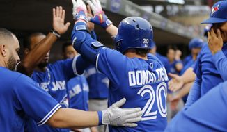 Toronto Blue Jays' Josh Donaldson (20) is congratulated in the dugout following his solo home run off Minnesota Twins pitcher Adalberto Mejia in the first inning of a baseball game Saturday, Sept. 16, 2017, in Minneapolis. (AP Photo/Jim Mone)